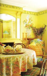 A hívogatóan üde ebédlő vidám tavaszi színharmóniája izgalmas ellentétet képez a fal és mennyezet klasszikus kiképzésével. A világos színű fabútorok szépen simulnak a sárga falhoz. Jól mutat a több különféle mintájú, de azonos könnyű vászonból készült textil is. A festett, antik római falfestményt idéző virágcsokor és a körben futó fríz is a legszebb tavaszi színekből készült.