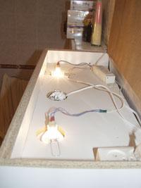 Beépített halogén rendszer fürdőszobai szekrényben. Az égők a felső zárt szekrényrekeszbe szellőznek. Itt kapott helyet a trafó is.
