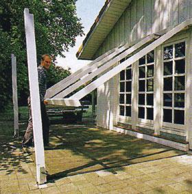 Az előre összeerősített tartókeretet a ház falába hajtott csavarra támasztva kell felemelni, majd a támoszlopokra helyezve már szilárdan rögzíthető az egész szerkezet