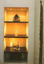 A falfülkében létrehozott vitrin érdekessége az oldalsó világításban rejlik. A minimalista formarendszerhez ennél több tárgyat nem is szabad ide elhelyezni