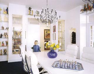 A naiv művészeti tárgyakat tartó nyitott polcok és üveges vitrinek tökéletes hátteret biztosítanak a hófehér ebédlőasztalnak