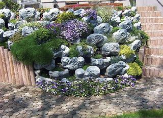 Növényekkel beültetett rézsűs kőtámfal