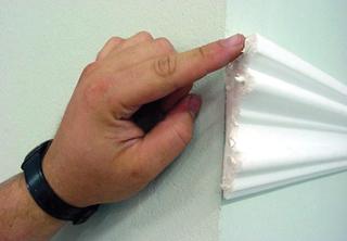 A falon már szintbe illesztett idomléc illesztési felületén a ragasztó egyenletes elterítése ujjbeggyel a legkönnyebb