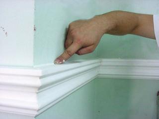 (a) A már falra ragasztott lécek alól kitüremlő ragasztó felesleges részét felül és alul is ujjal elsimítás közben kell eltávolítani