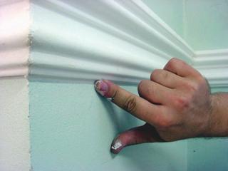 (b) A már falra ragasztott lécek alól kitüremlő ragasztó felesleges részét felül és alul is ujjal elsimítás közben kell eltávolítani