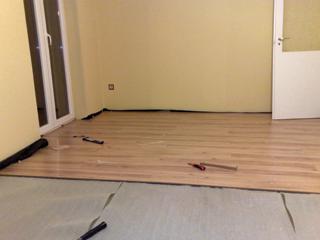 Az aljzatra terített alátétfóliára kerülnek a laminált padlólapok