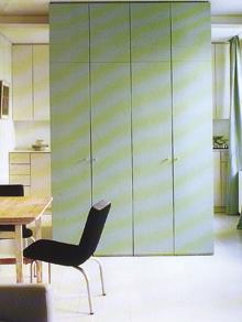 A konyha és az ebédlő közötti beépített szekrény ebben az egyterű lakásban a gardrób funkcióját is ellátja.