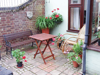 Ahol pihenő funkciója is van a kis előkertnek, elég lehet egy-két dézsás növény, hogy életet vigyen az épített környezetbe