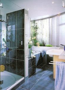 Egy nagyobb alapterületű fürdőben elfér a zuhany és a kád is. A térelválasztó falba előrehúzható kis polcokat építettek mindent cm-t kihasználva