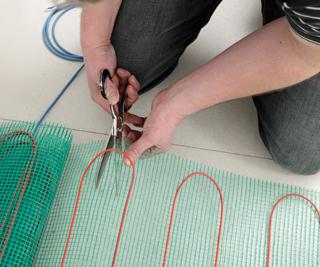 A helység másik falához érve elvágjuk a fűtőszőnyeget, úgy hogy a fűtőkábel ne sérüljön